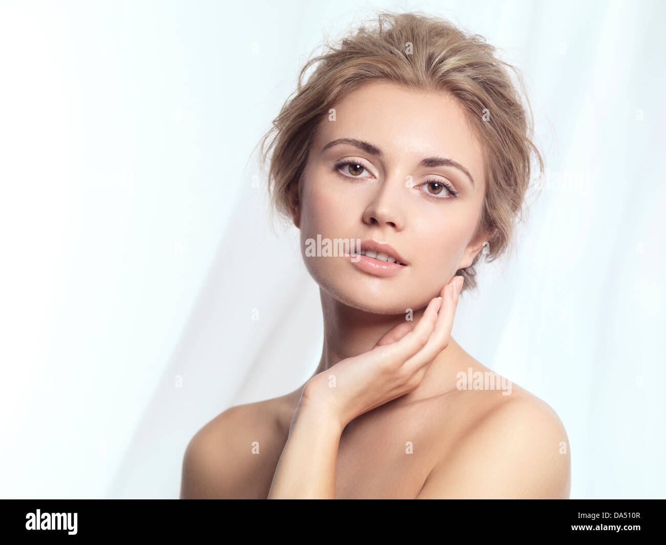 Beauty portrait of a young woman relaxed face with natural clean makeup and contemporary hairstyle over white flowy - Stock Image