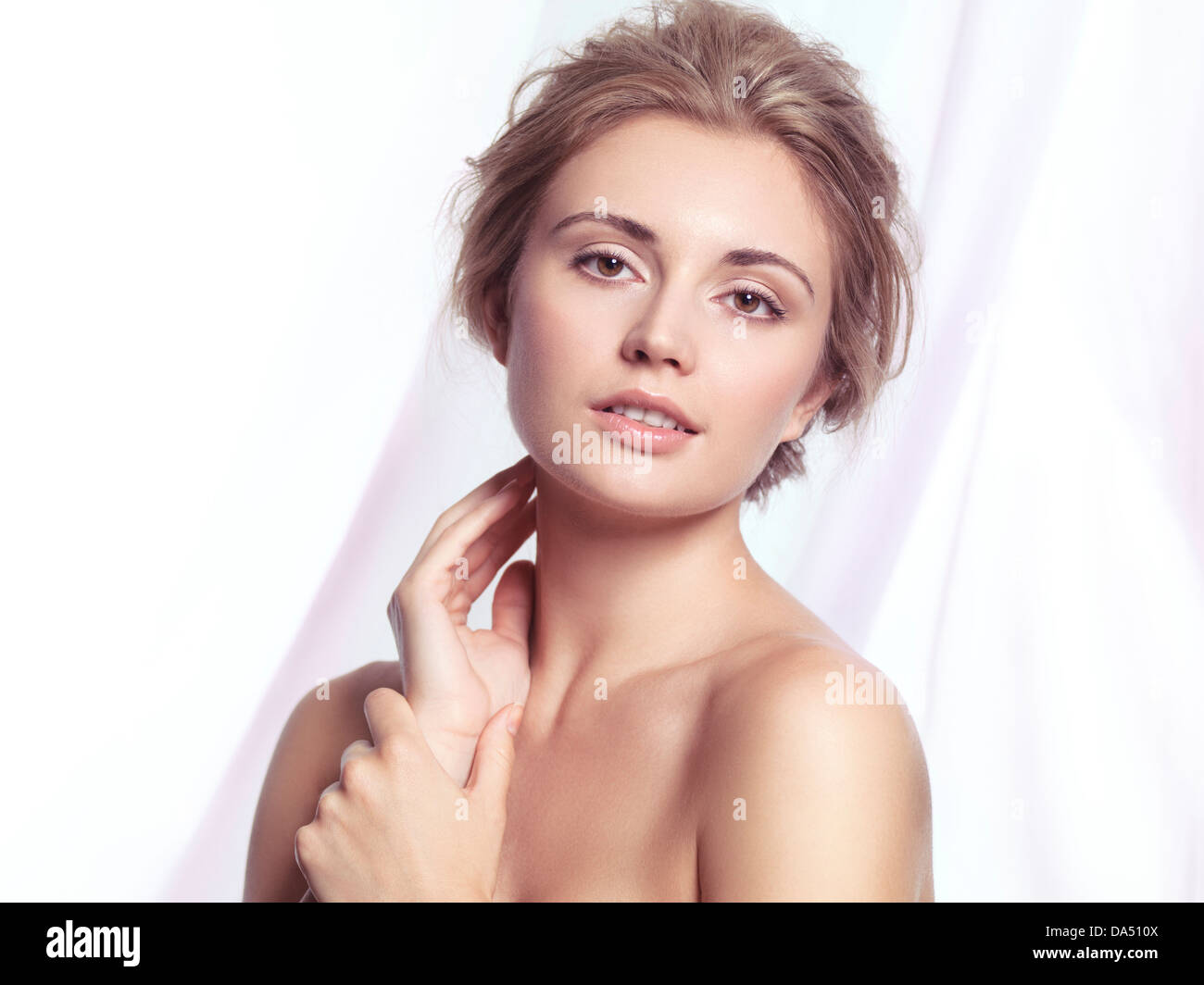 Beauty portrait of a young woman relaxed face with natural clean makeup and contemporary hairstyle over light pink - Stock Image