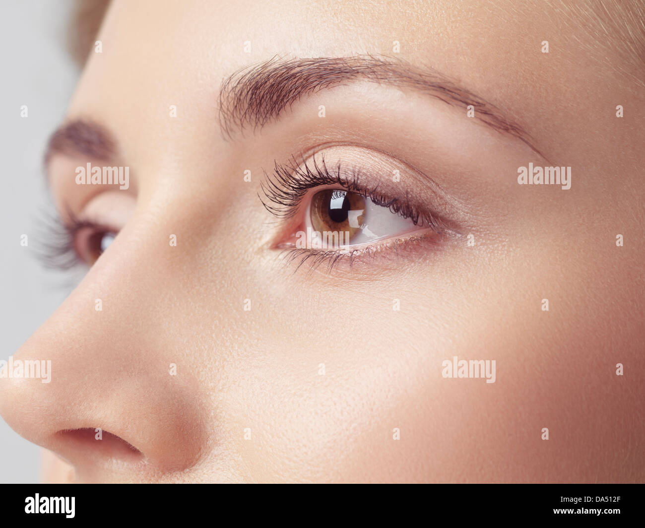 Young woman face closeup of brown eyes - Stock Image