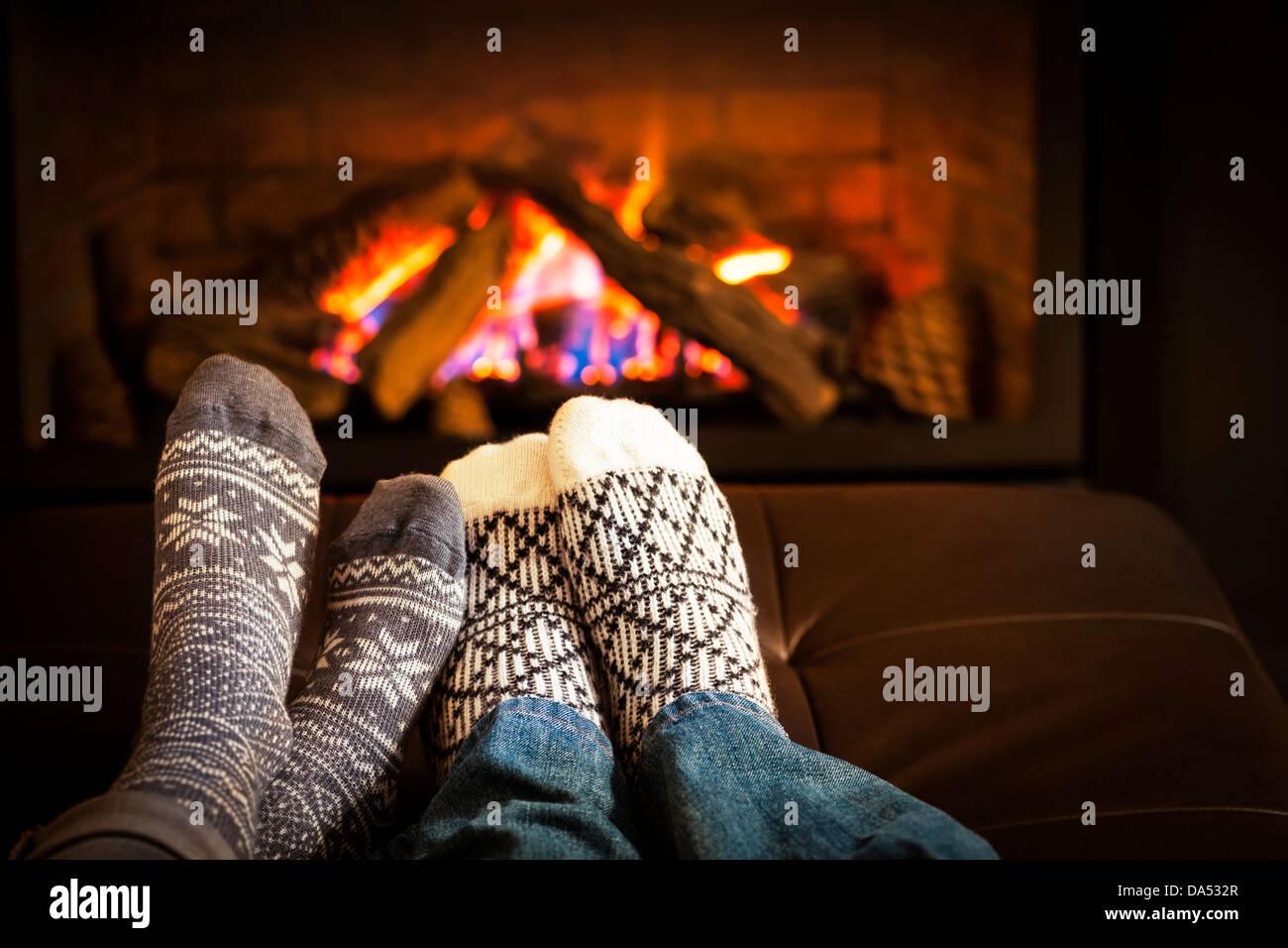 Feet in wool socks warming by cozy fire - Stock Image