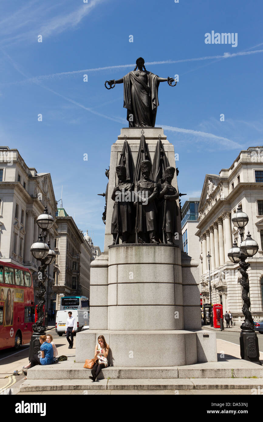 People relaxing under the Crimean War Memorial, Waterloo Place, London, England, UK - Stock Image