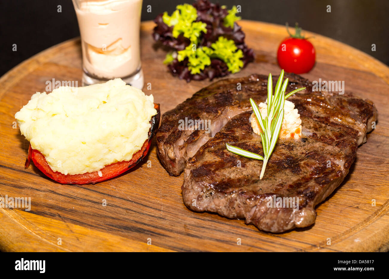 Beef steak cooking on the grill - Stock Image
