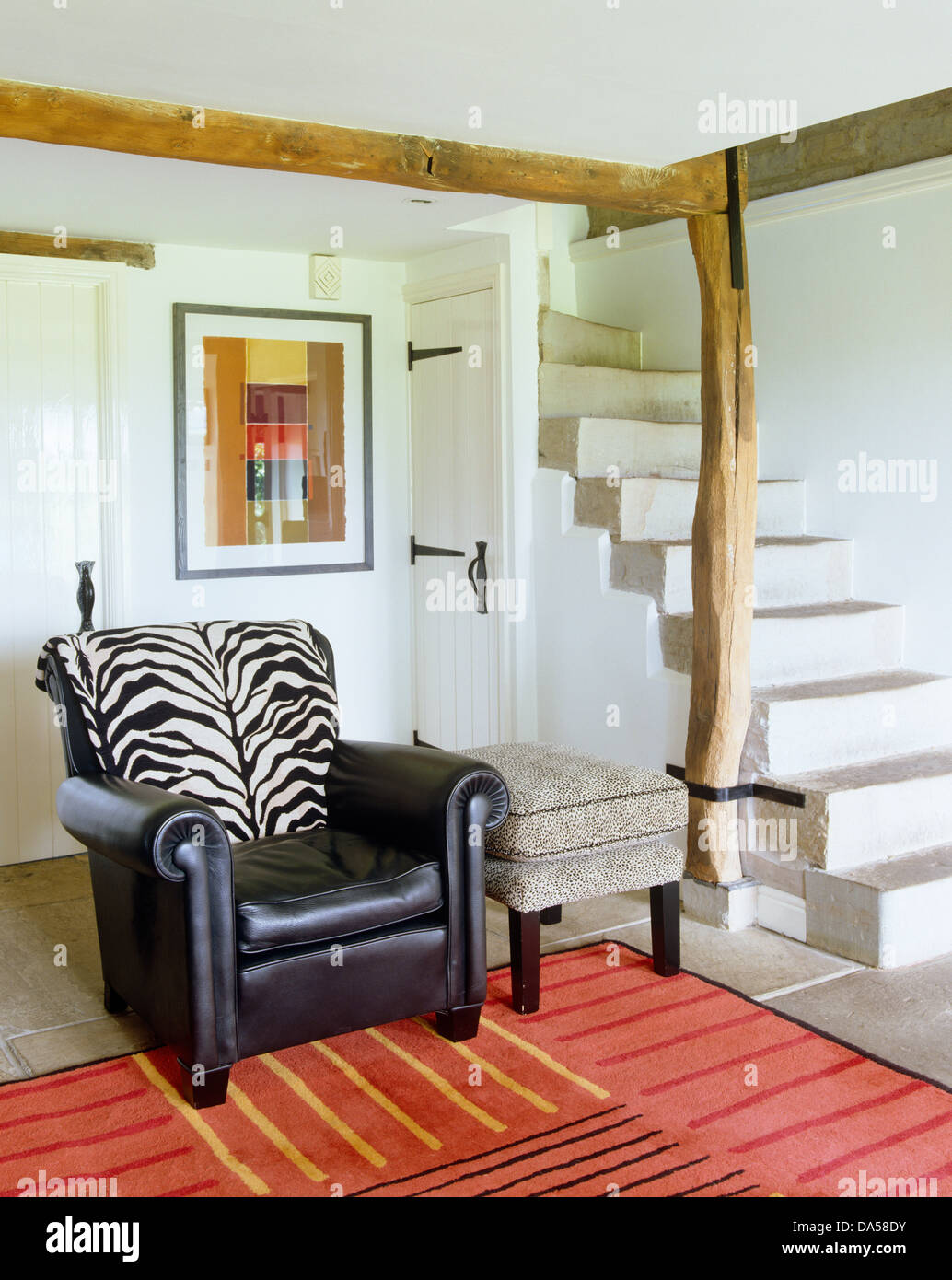 Zebra Print Cushion On Black Leather Armchair In Contemporary Cottage Hall  With Red Rug And Stone Stairs