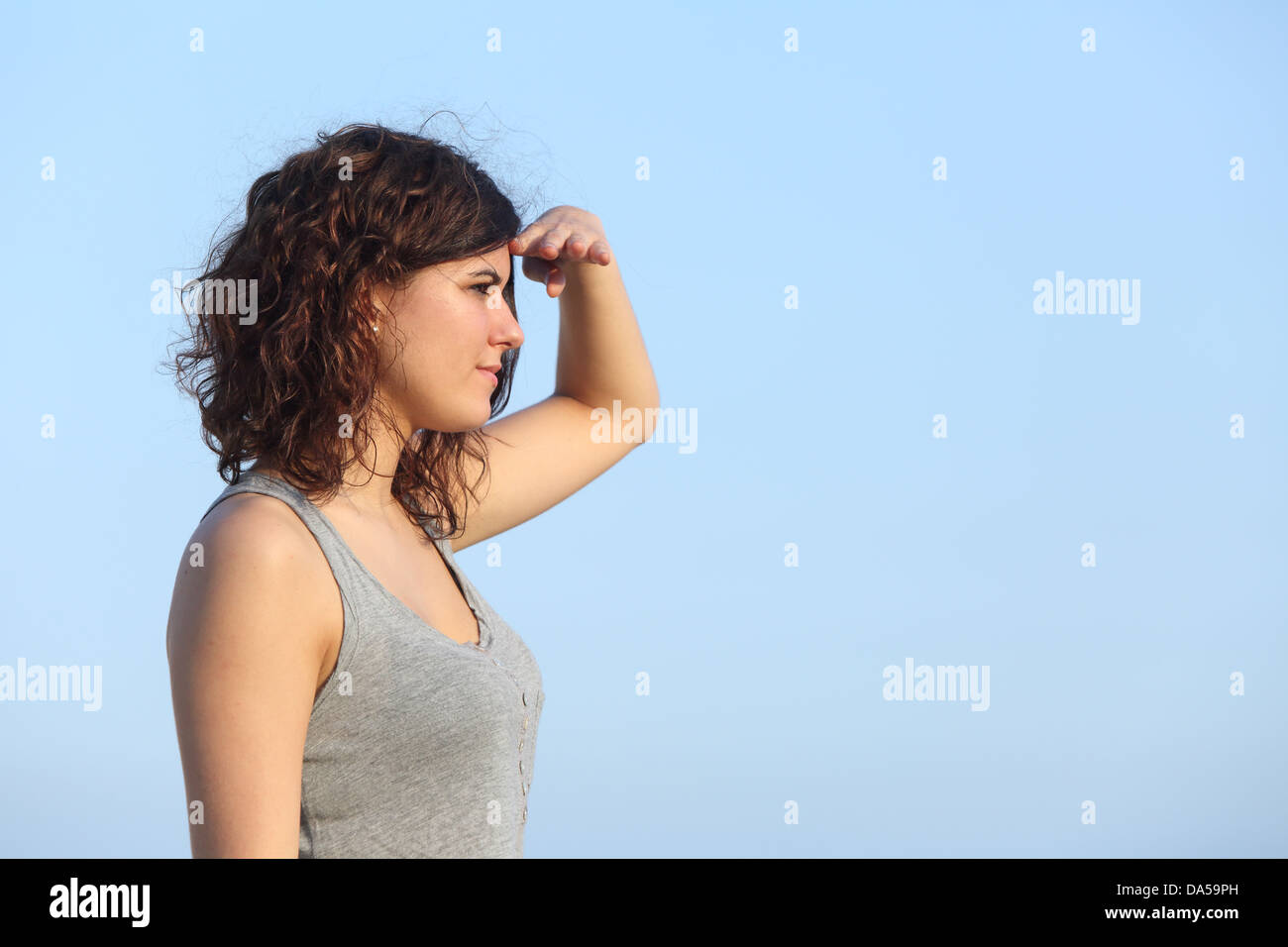 Attractive woman looking ahead with the hand in forehead with the blue sky in the background - Stock Image