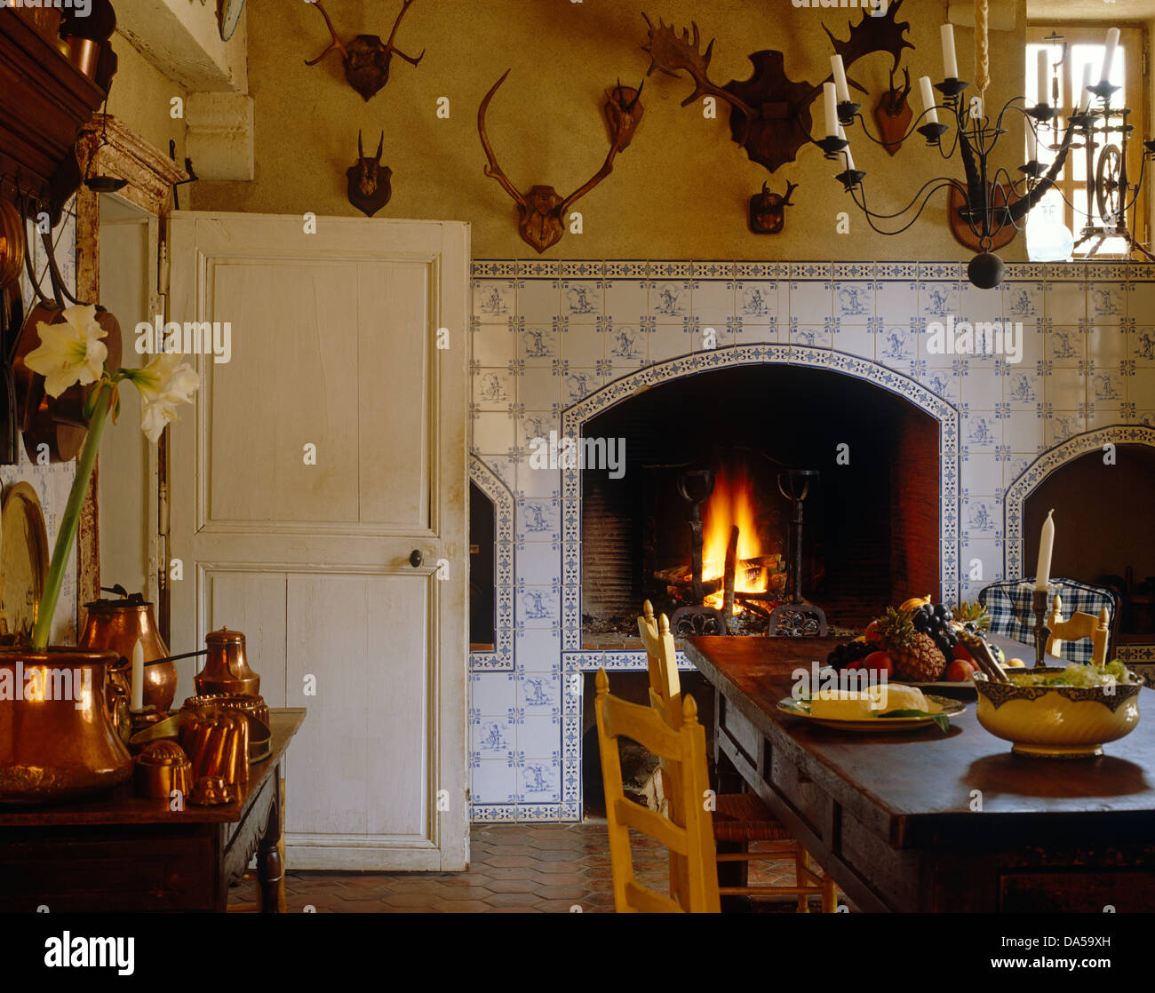wooden table and chairs in french country kitchen with display of antlers above open fire in recess in bluewhite tiled wall - Kitchen In French