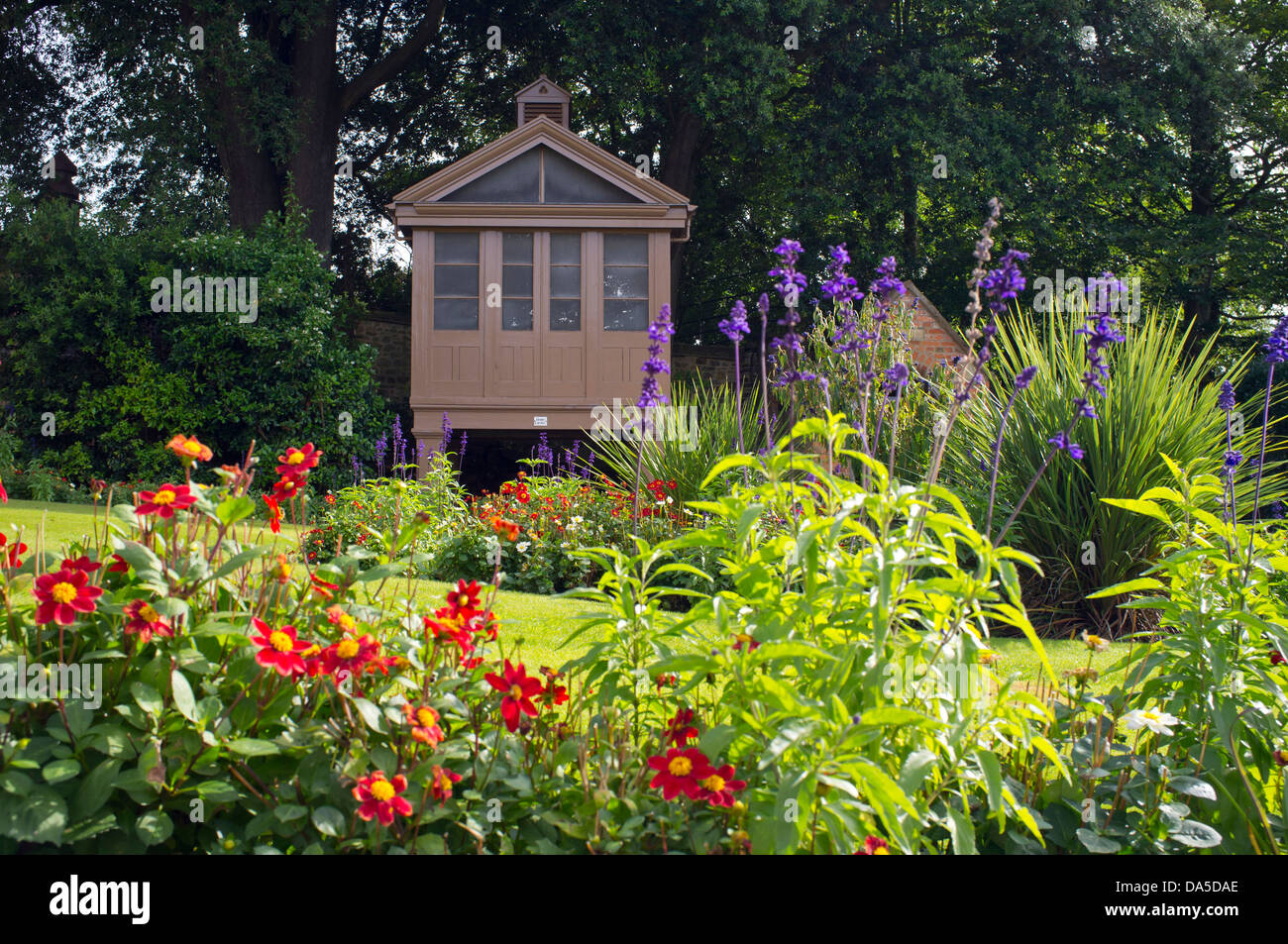 Flower beds with flowering shrubs and annuals in the borders with a flower beds with flowering shrubs and annuals in the borders with a garden shed on stilts in the shade izmirmasajfo