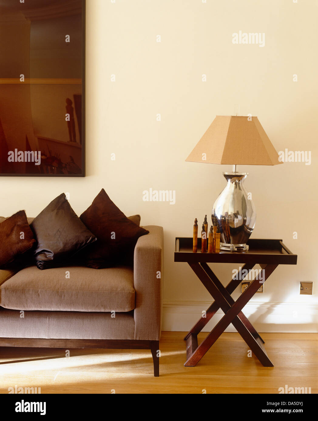 Silver lamp with beige shade on dark wood side table next to beige silver lamp with beige shade on dark wood side table next to beige sofa in modern living room aloadofball Image collections