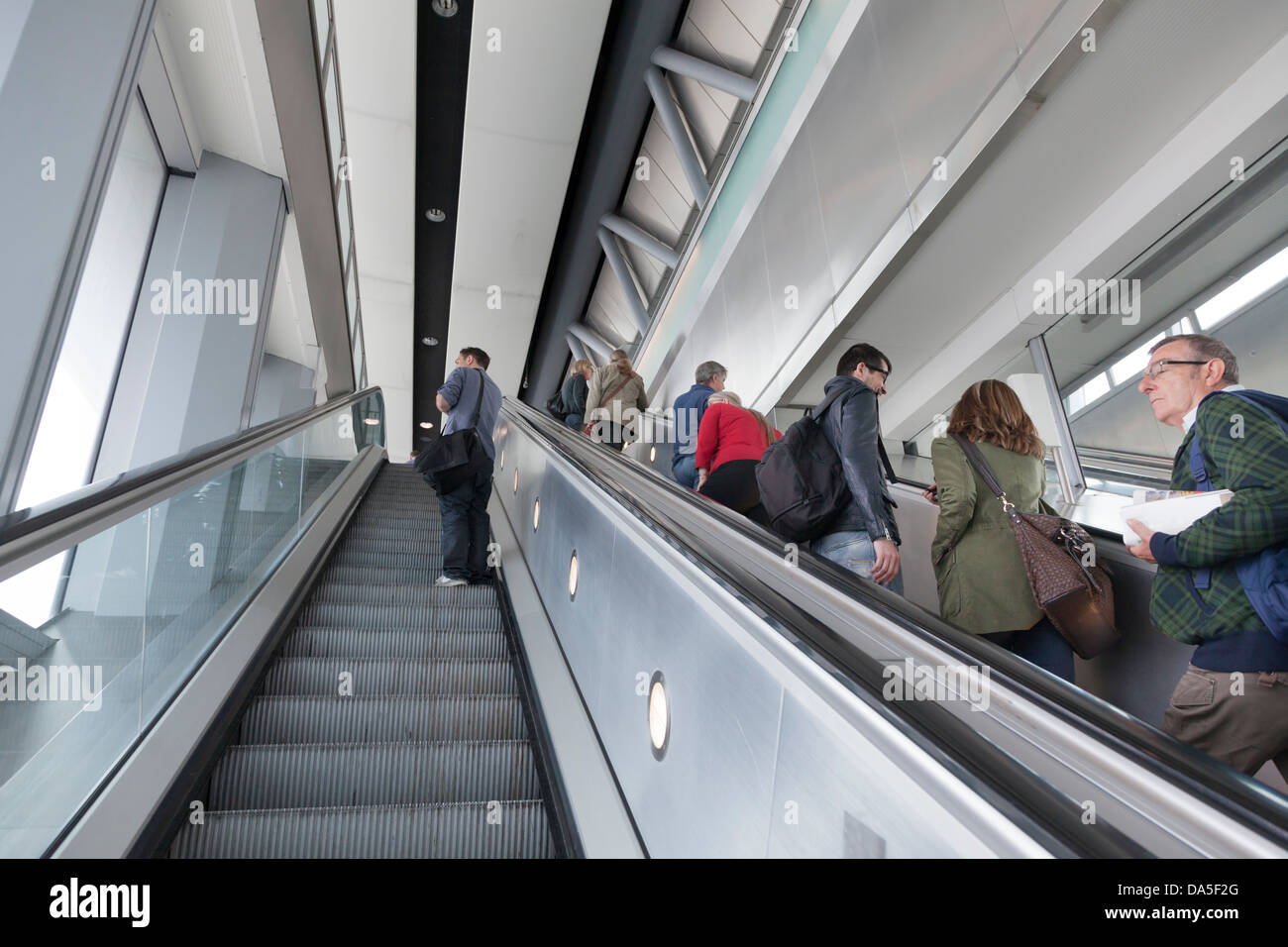 passengers on up escalator at airport - Stock Image