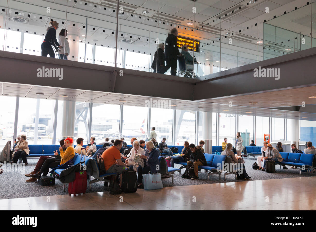 passengers waiting in airport departure lounge below arrivals corridor - Stock Image