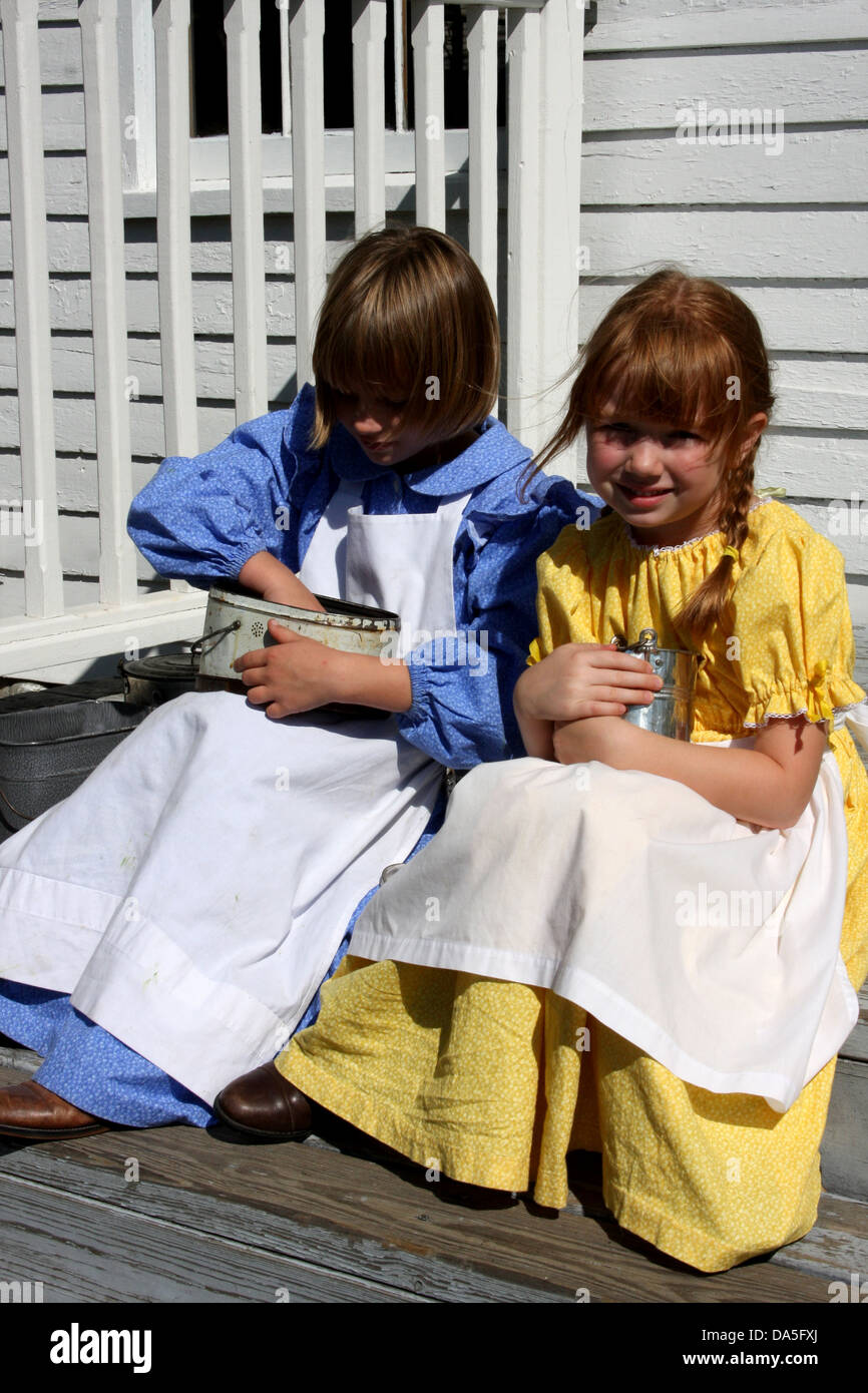 Two young children eating their lunch from lunch pales on an historic school house steps Stock Photo