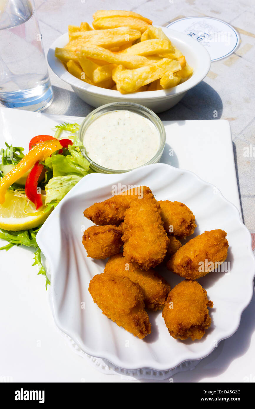A simple pub lunch of breaded Scampi with tartare sauce lemon, salad garnish and chips - Stock Image