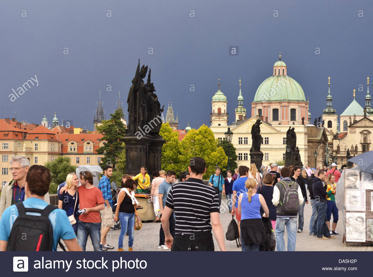 Prague Czech Republic - people walking across the historical Charles Bridge with dark sky above. - Stock Image