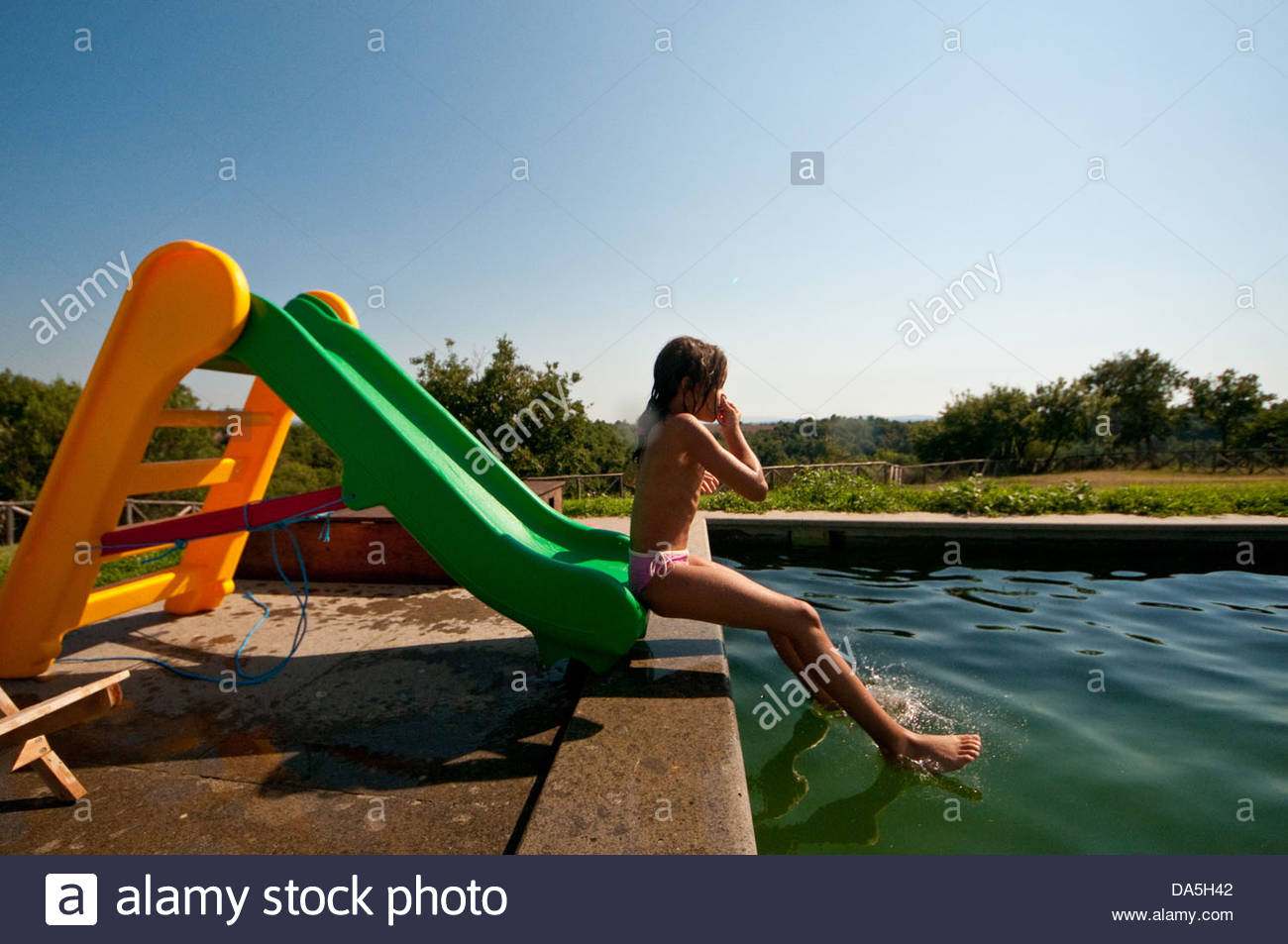 girl in the pool on a slide Stock Photo