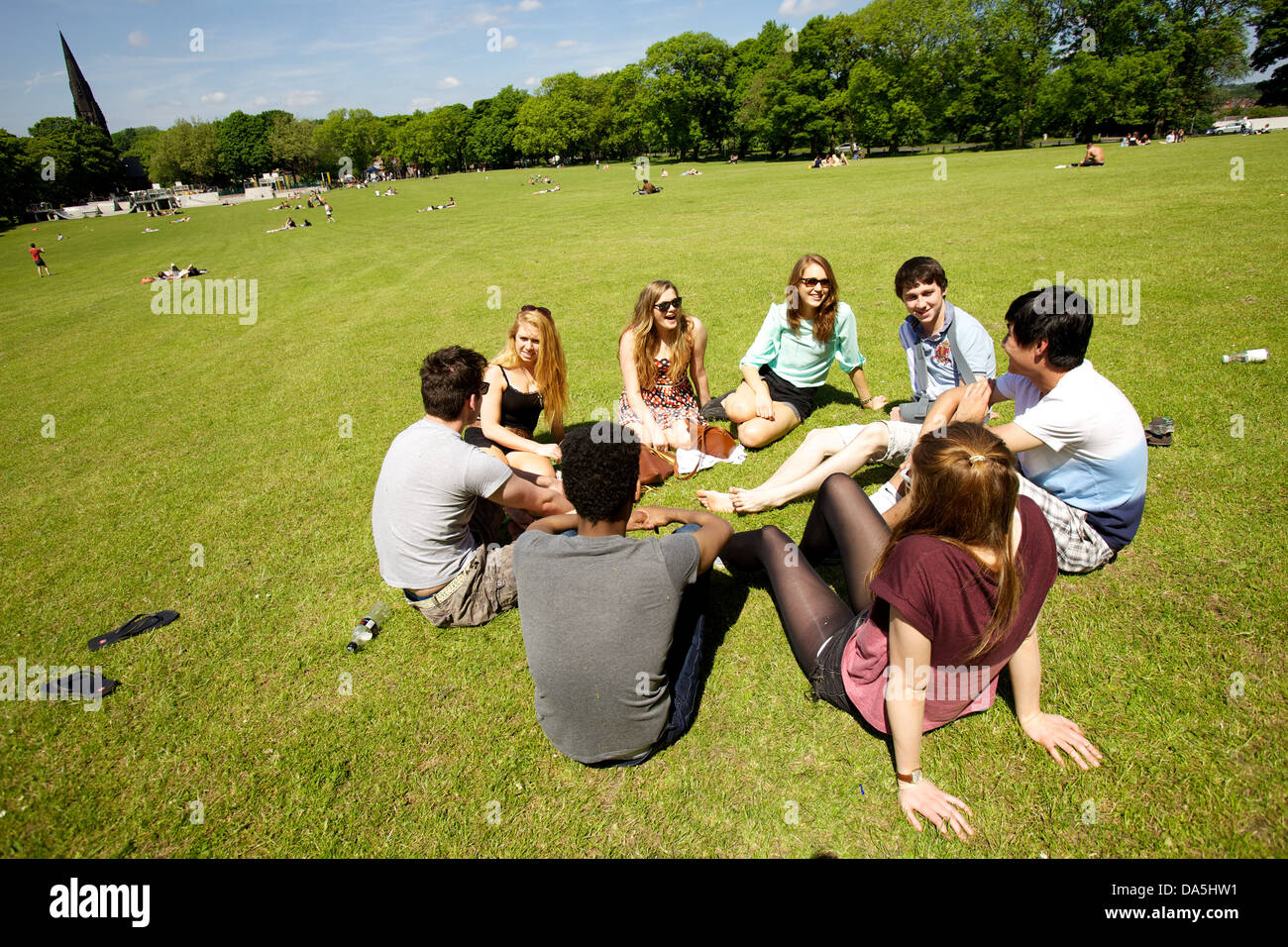 group of students in park on sunny day - Stock Image