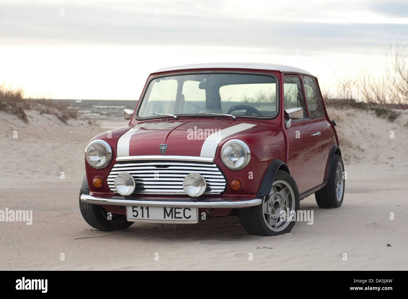 A classic Mini on a beach. - Stock Image