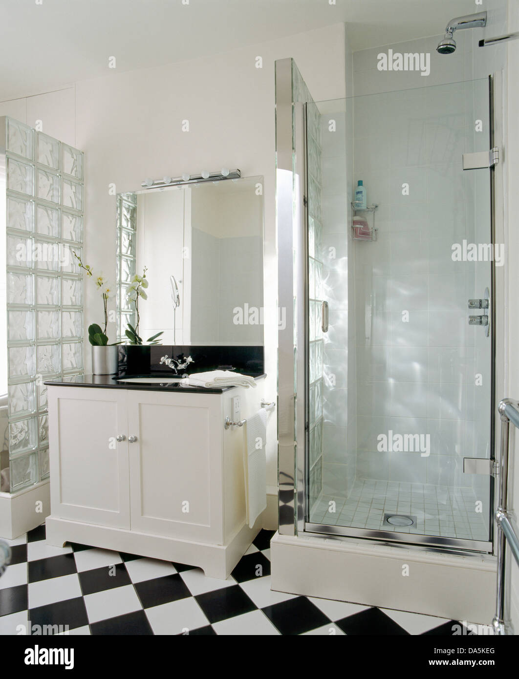 Mirror above wash basin in white vanity unit beside glass shower ...