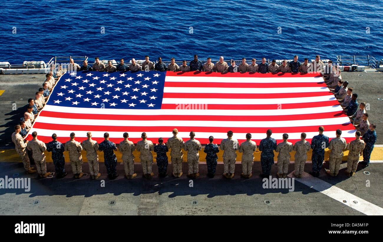 US Marines and Sailors hold the American flag to commemorate Independence Day on the flight deck of the USS Kearsarge - Stock Image