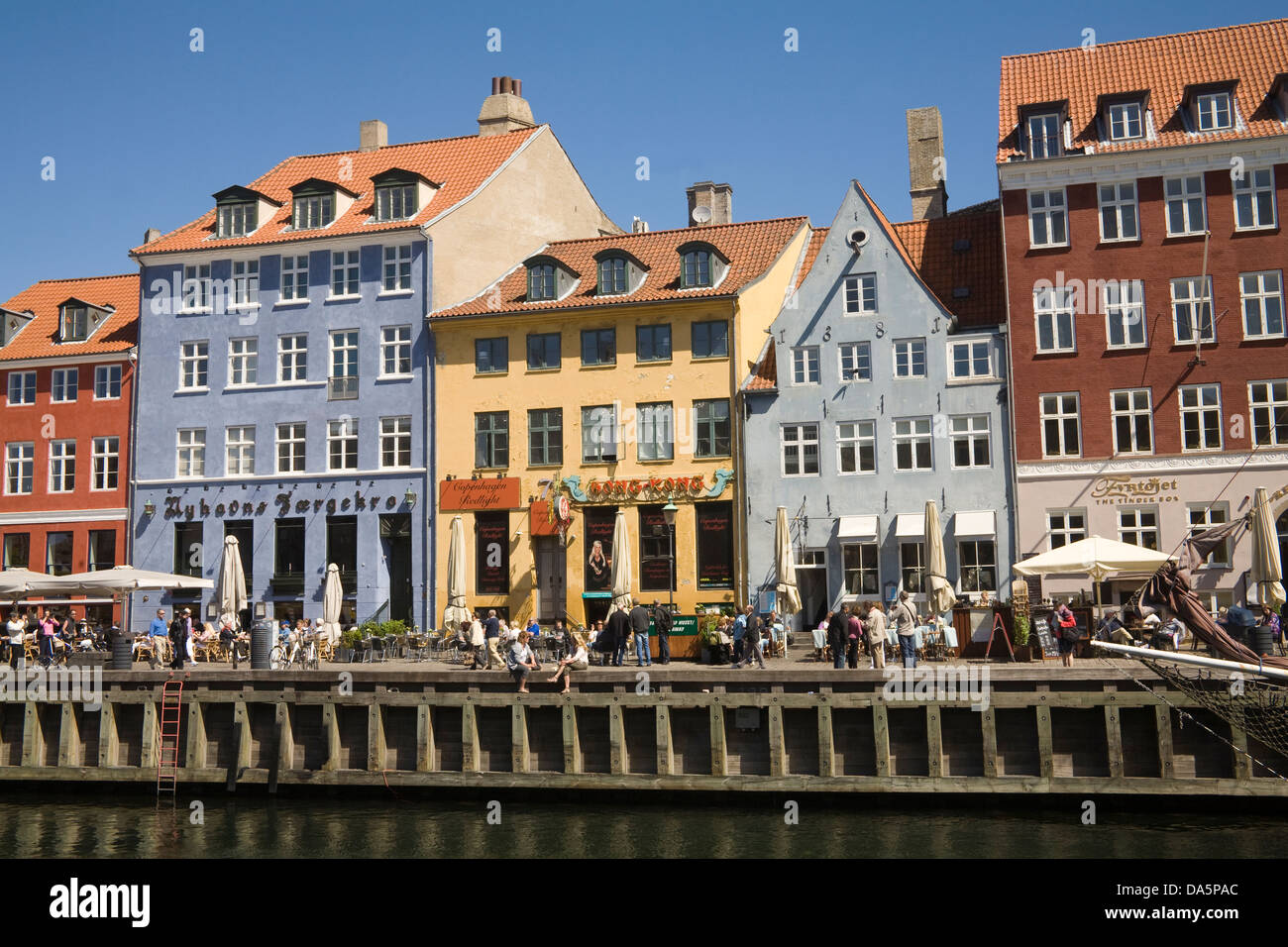 Copenhagen Denmark EU 17thc building with colourful facades in Nyhavn with open air cafes and restaurants on canal - Stock Image