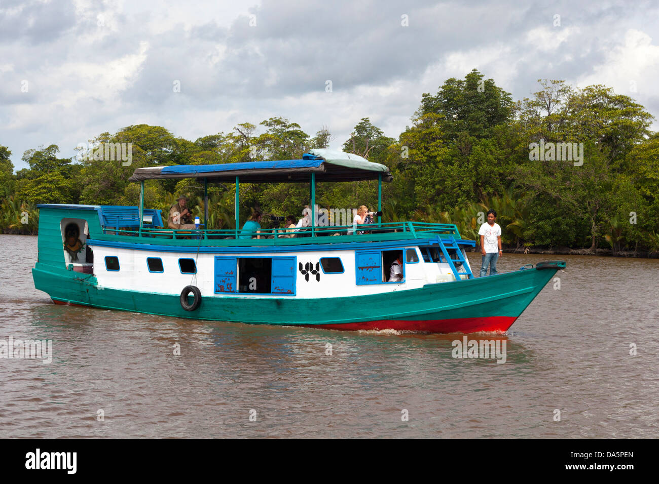 Indonesian guide and tourists on a klotok, a traditional  river boat, on the Kumai River in central Kalimantan - Stock Image