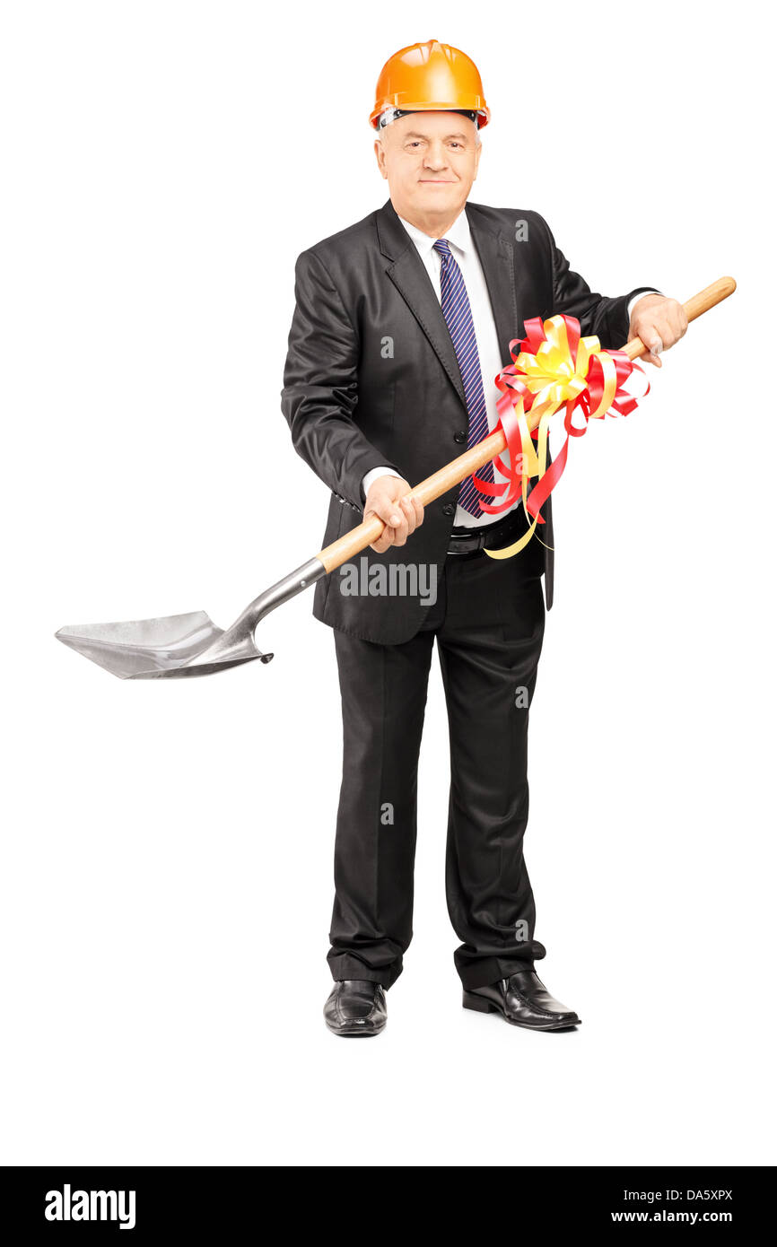 Full length portrait of a mature businessman with helmet holding a shovel with ribbon on it isolated on white background - Stock Image