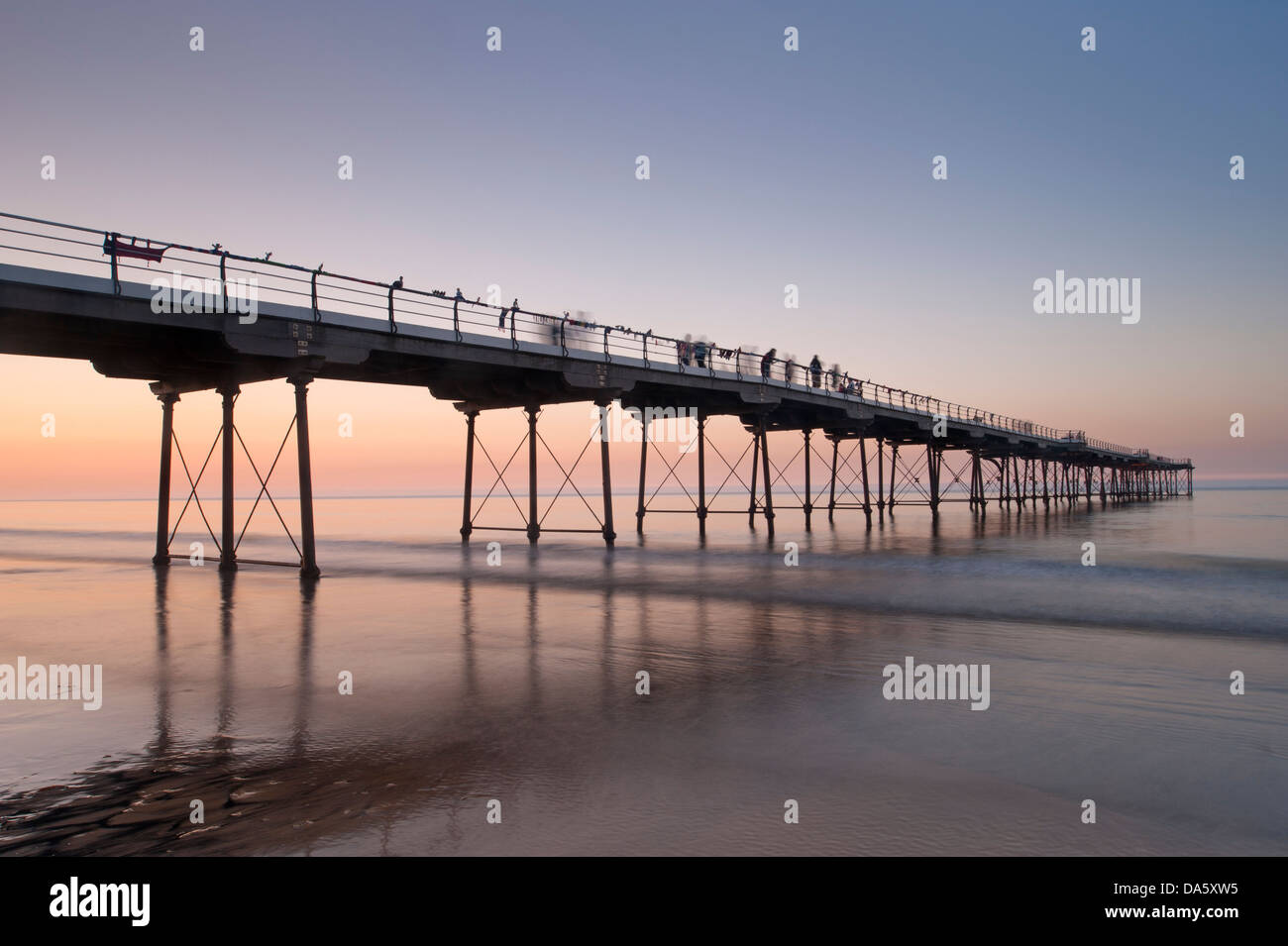 Under colourful summer sunset sky, view from sandy beach of people walking on historic seaside pier over calm sea - Stock Image