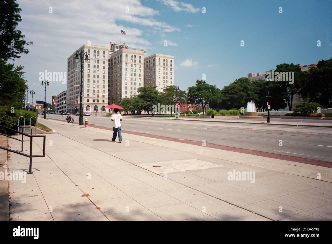 Man walks west on Woodward Avenue in Midtown Detroit with a red umbrella - Stock Image