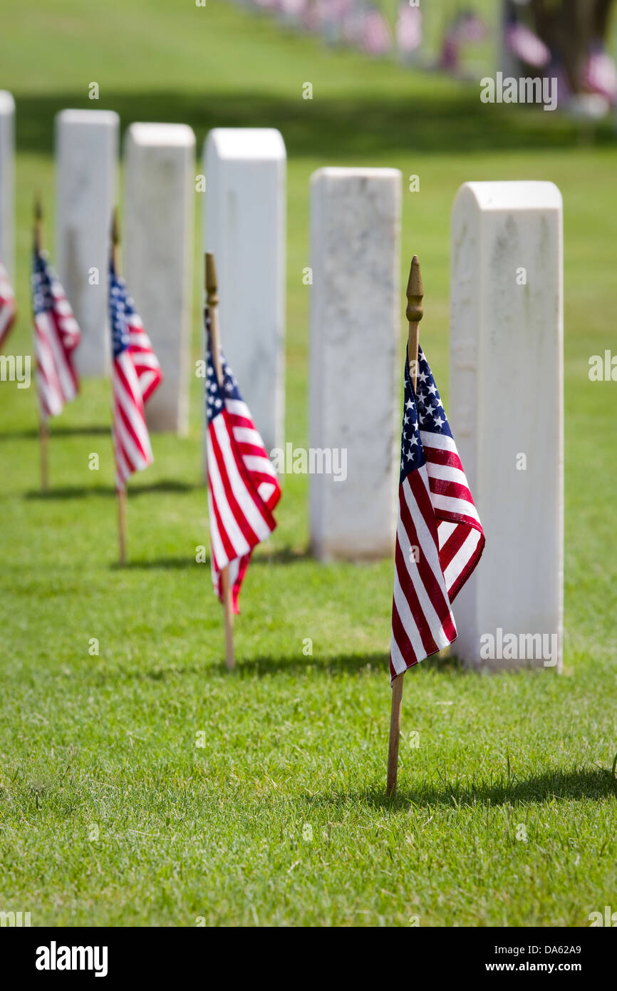 American flags on gravesites commemorate Memorial Day at a United States national cemetery. Stock Photo
