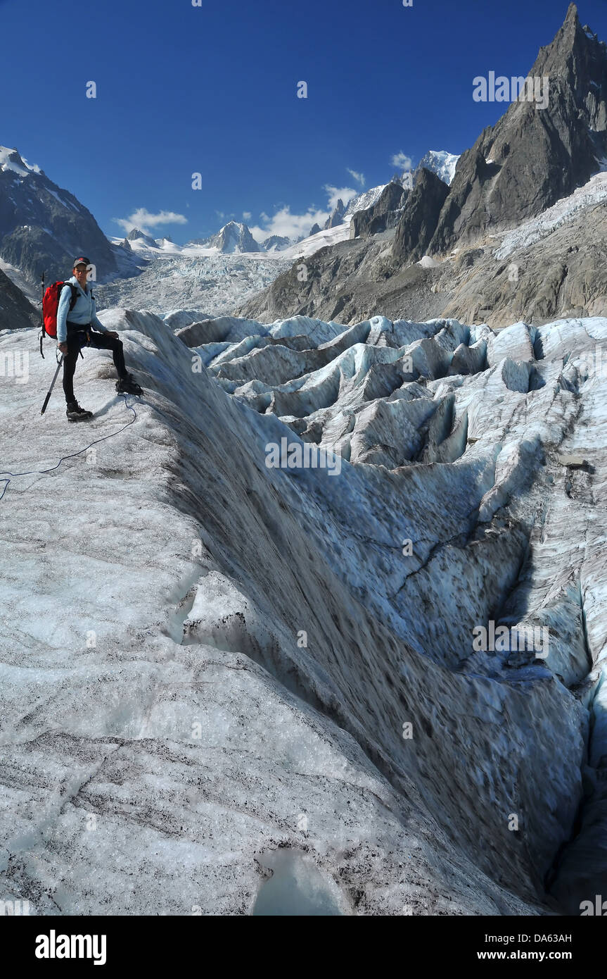 A woman climber considers her options crossing a crevasse field on the 'sea of ice' or mer de glace in the - Stock Image