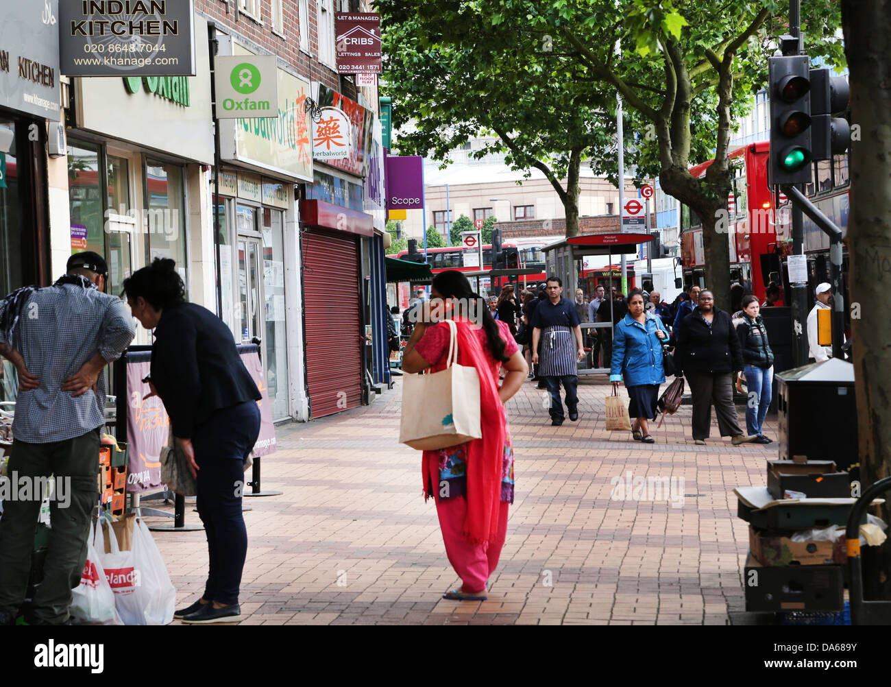 Morden London England People Shopping In High Street Asian Woman on Mobile Phone - Stock Image