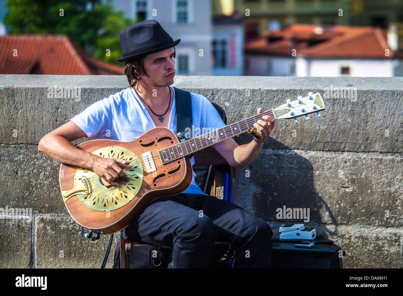 Street musician plays an Amistar Resophonic guitar on Charles Bridge, Karlův most, Prague, Praha - Stock Image