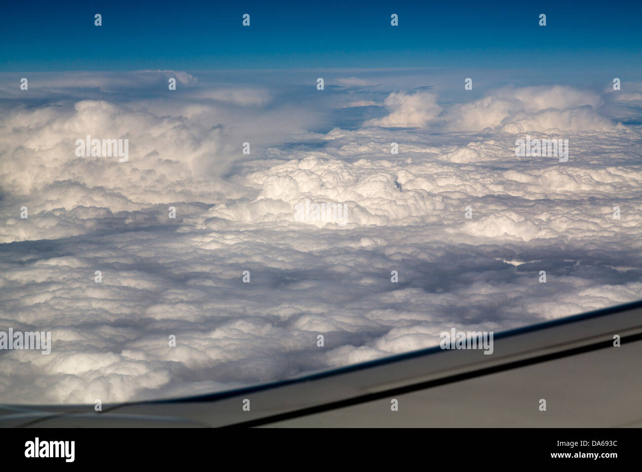 Wing of an airplane on cloud sky - Stock Image