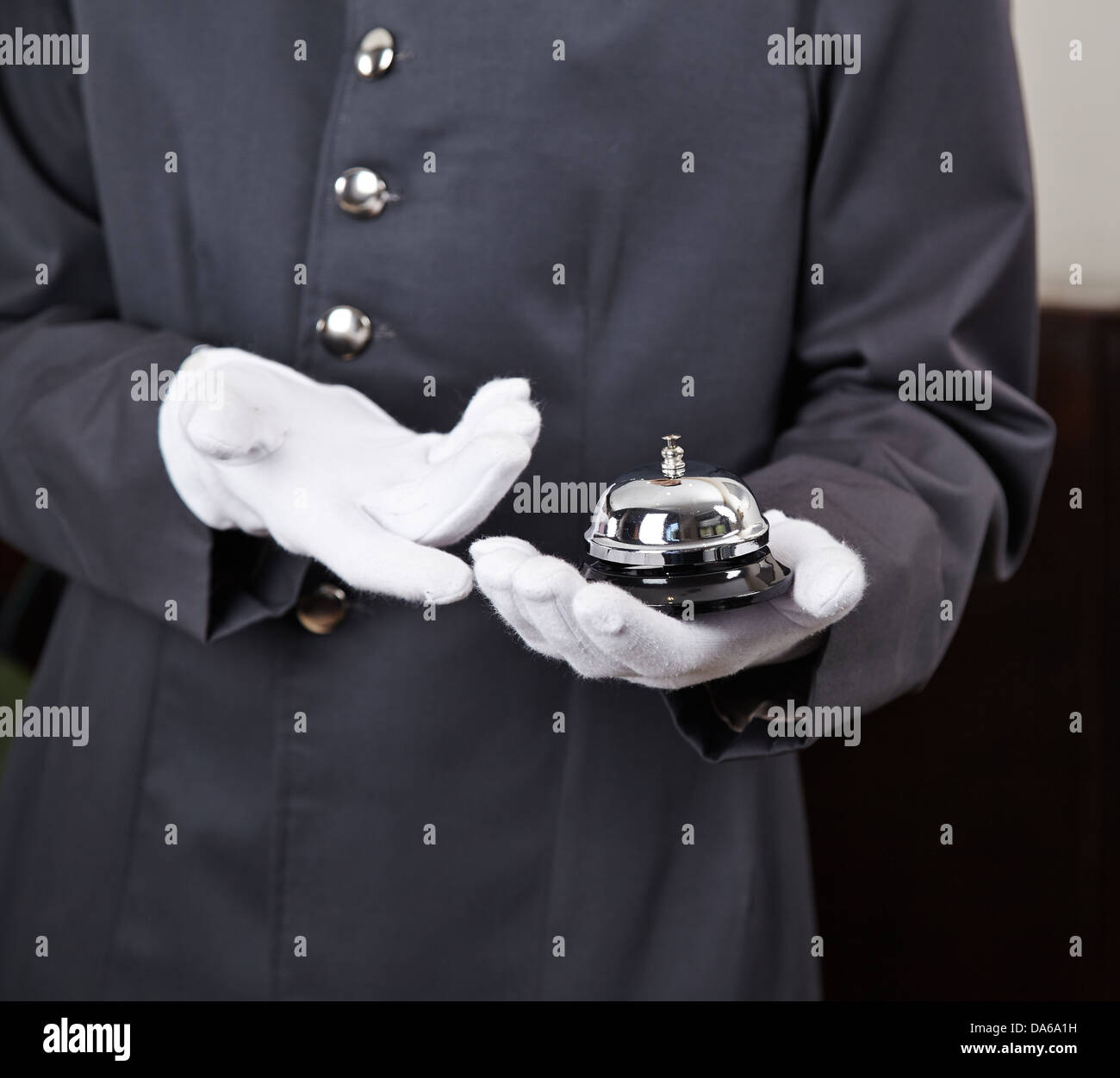 Bellboy holding bell in hotel on his hand - Stock Image