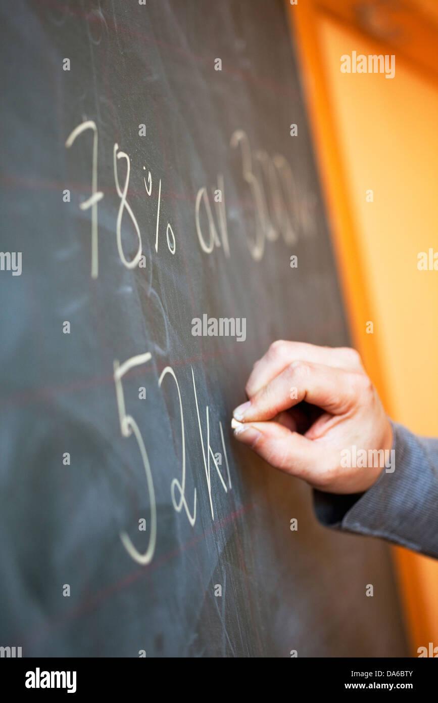 Close-up of teacher writing on blackboard - Stock Image