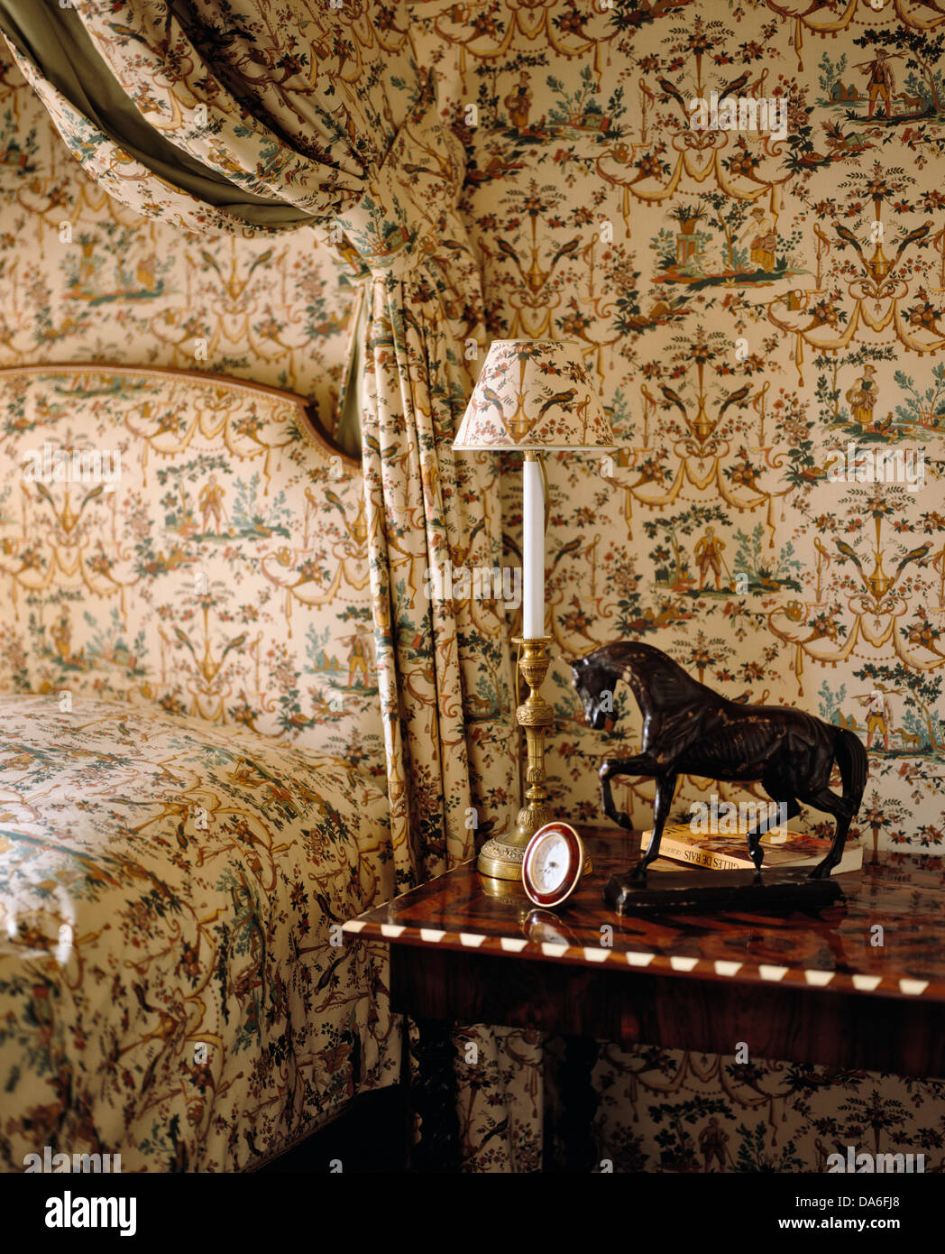 Coordinating wallpaper and bed drapes and headboard in country bedroom with small lamp and statue of horse on antique - Stock Image