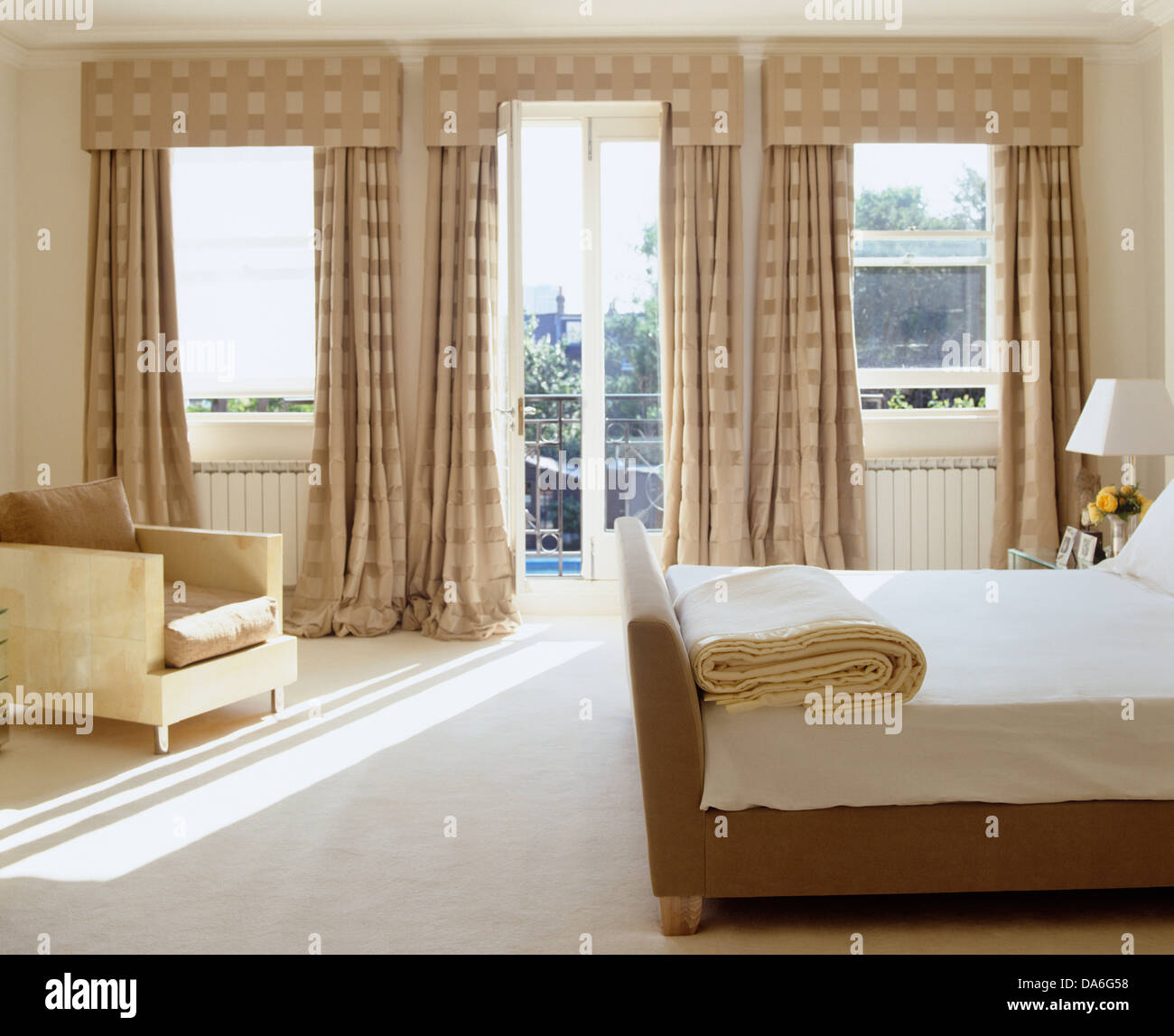 . Double bed and white carpet in contemporary bedroom with with