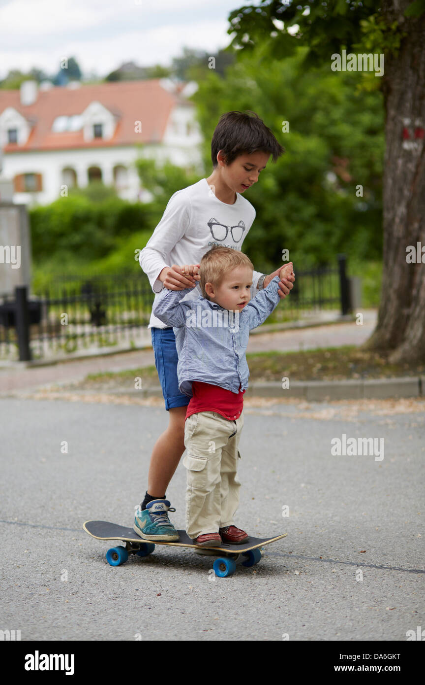Older and younger brothers riding a skateboard - Stock Image