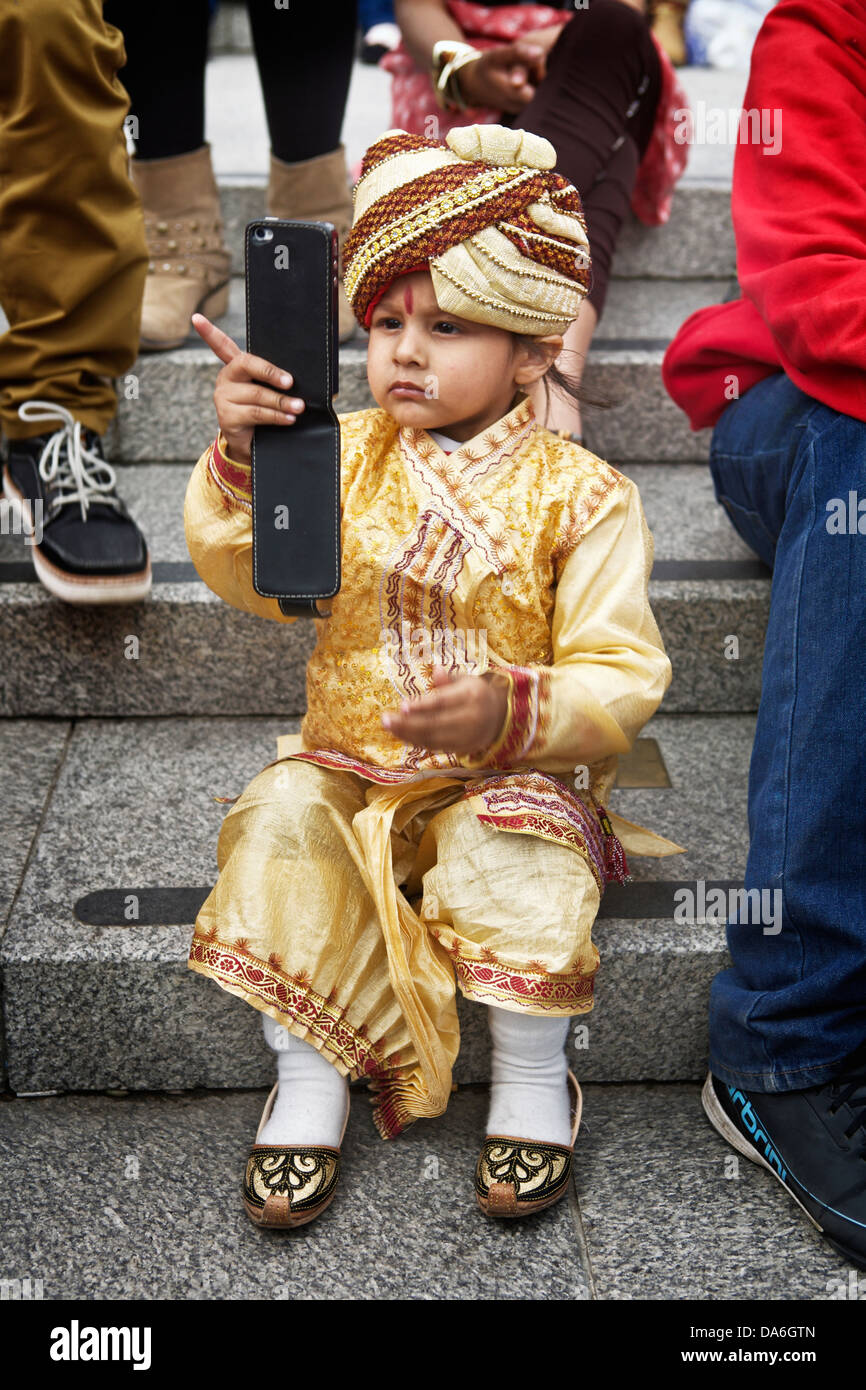 Portrait of a young boy sitting on steps using a mobile phone. - Stock Image