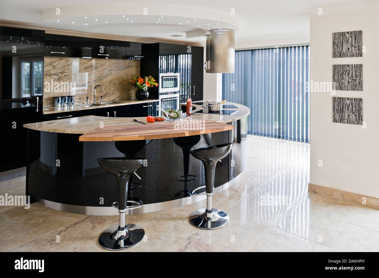 Pair Of Bomba Bar Stools At Breakfast Bar On Glossy Black Central Island  Unit In Modern Kitchen With Stone Flooring