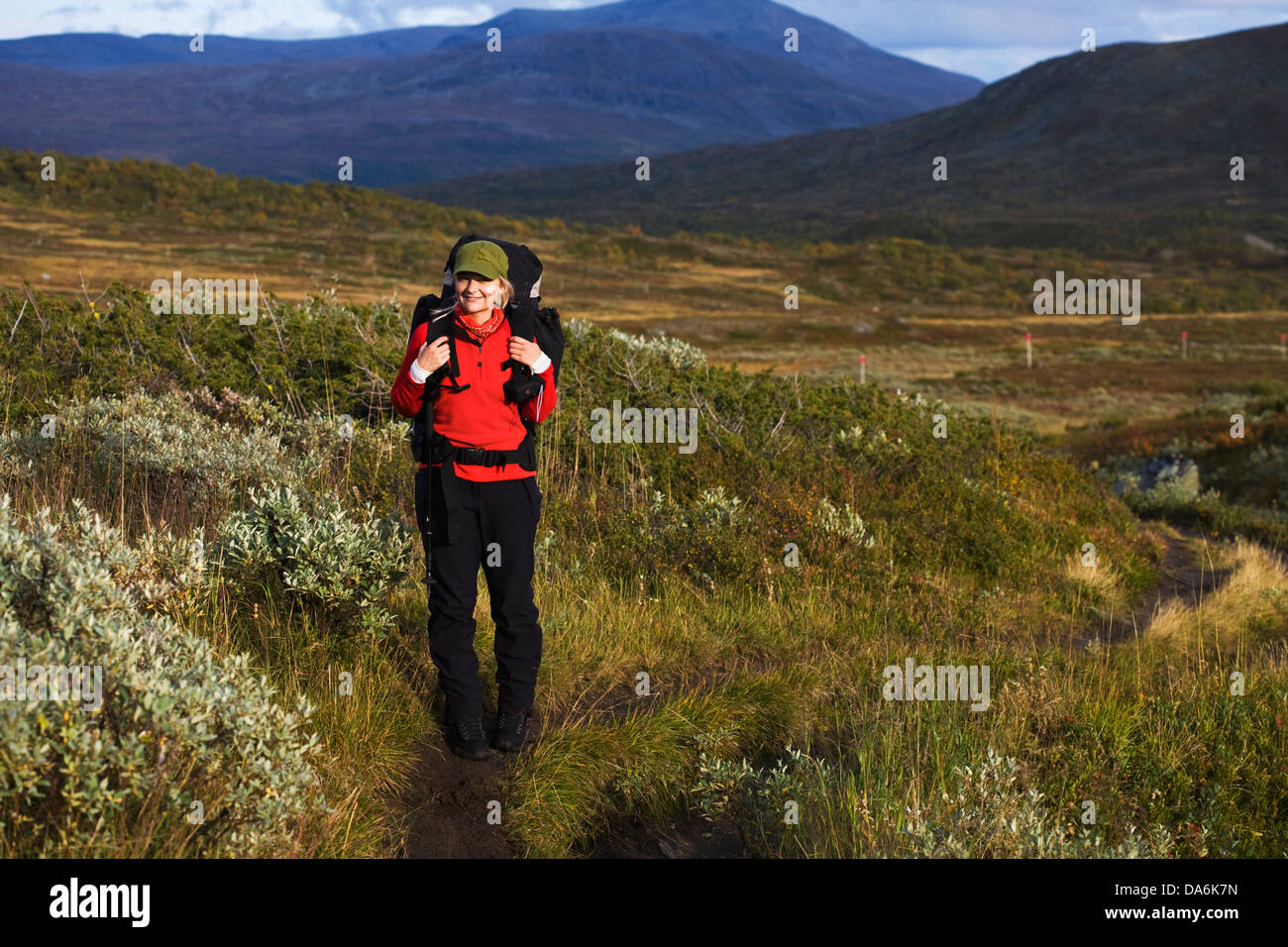 Woman hiking among hills - Stock Image