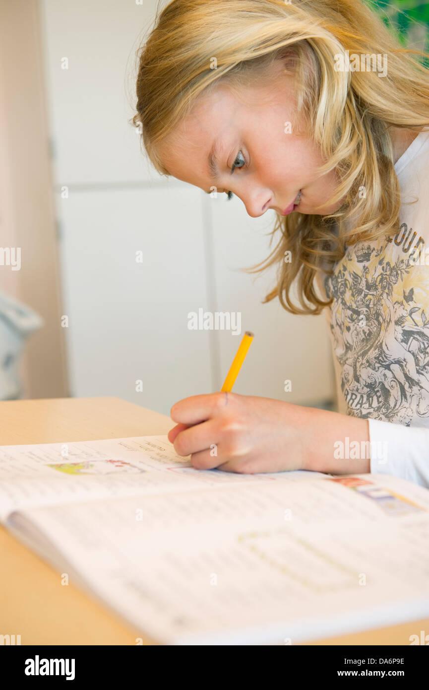 View of schoolgirl (10-11) writting - Stock Image