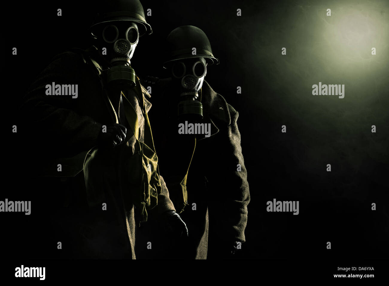 Soldiers with gas mask in a dark background - Stock Image