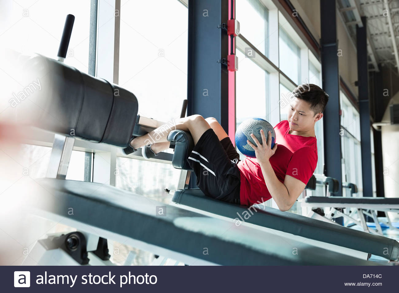 Man exercising with medicine ball at fitness center - Stock Image