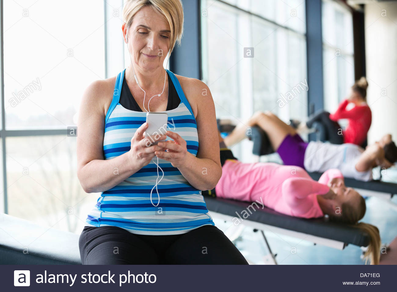 Woman listening to music on smartphone in fitness center Stock Photo