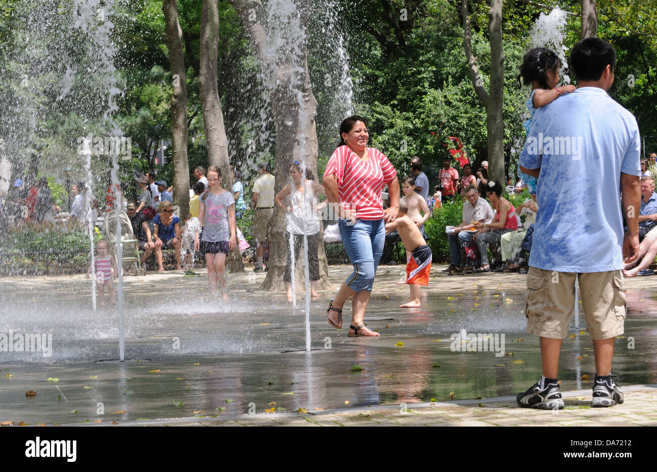On a hot, humid July 4, adults and children cooled off in a fountain in Battery Park, in lower Manhattan. - Stock Image