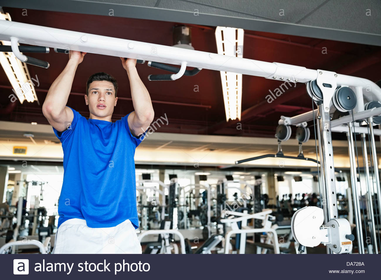 Man doing pull-ups in fitness center - Stock Image