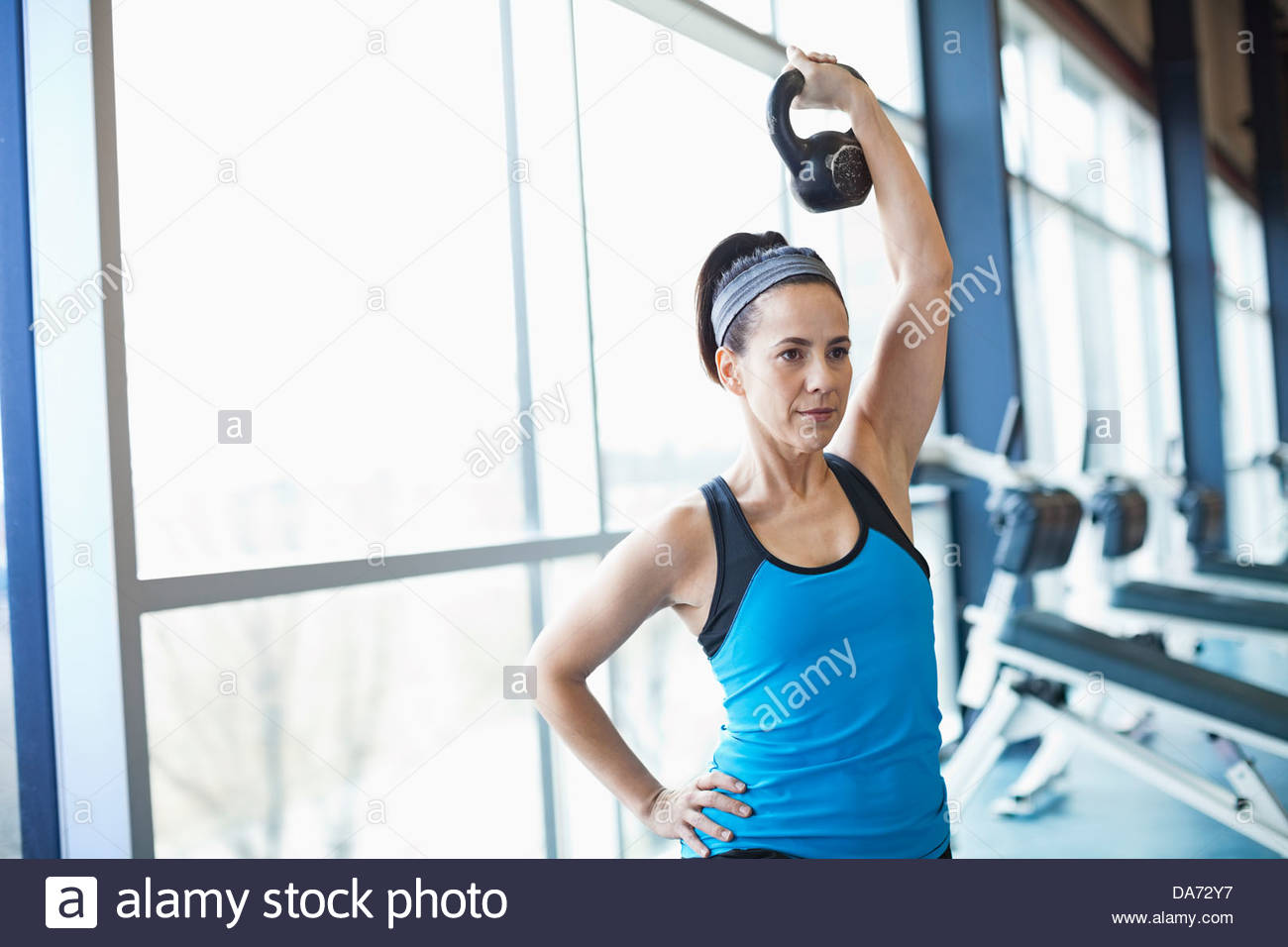 Woman exercising with kettlebell in fitness center - Stock Image