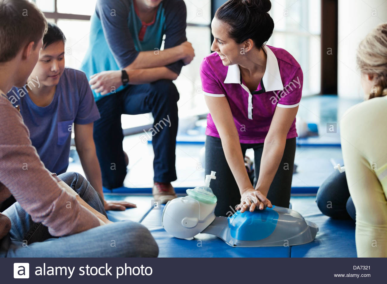 Instructor teaching CPR to class in fitness center - Stock Image