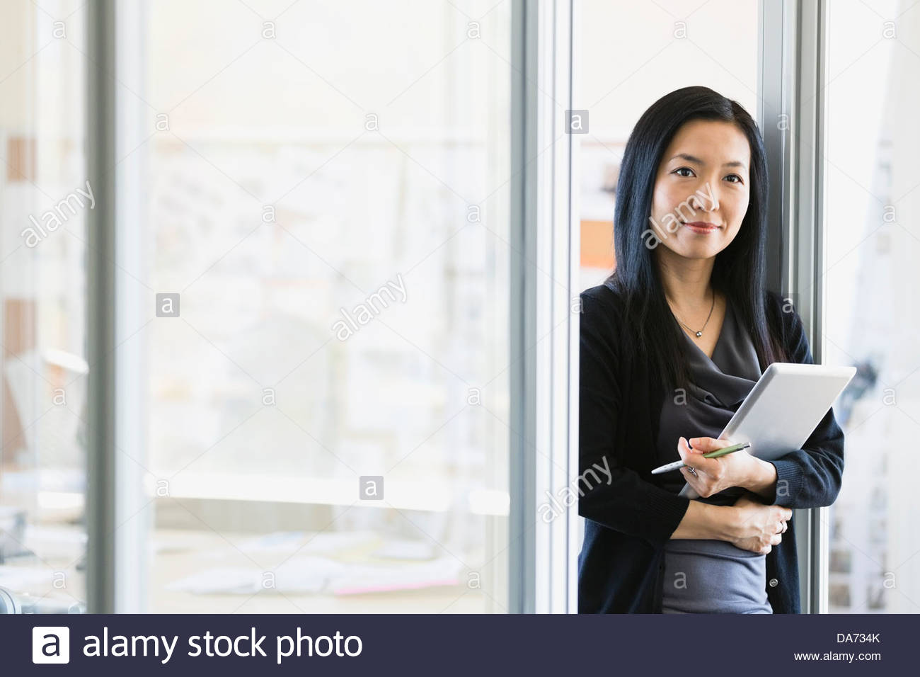 Businesswoman holding digital tablet in office - Stock Image