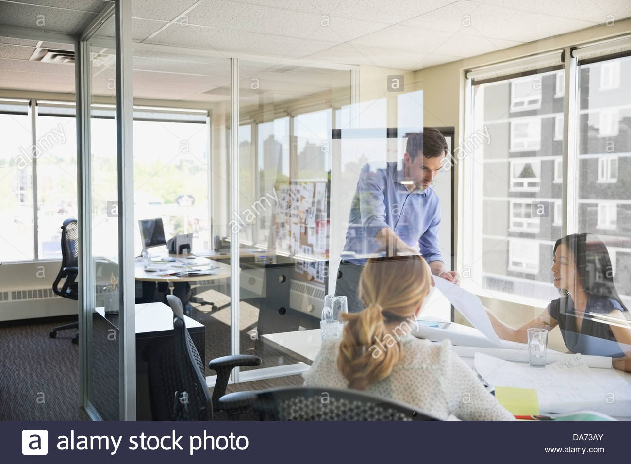 Business people working on project at desk in office - Stock Image