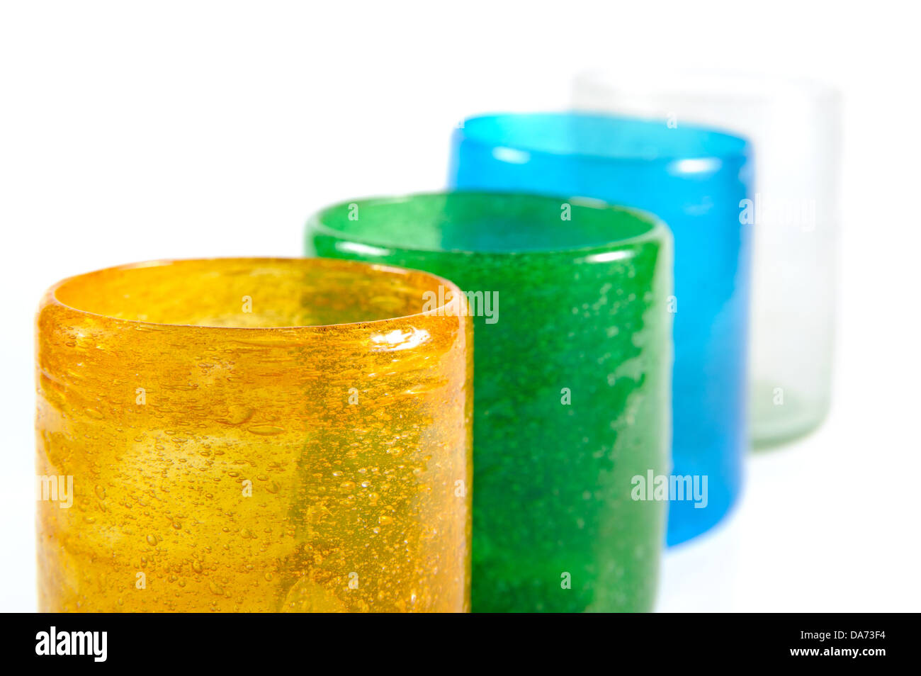 group of multi coloured glass cups on white background - Stock Image